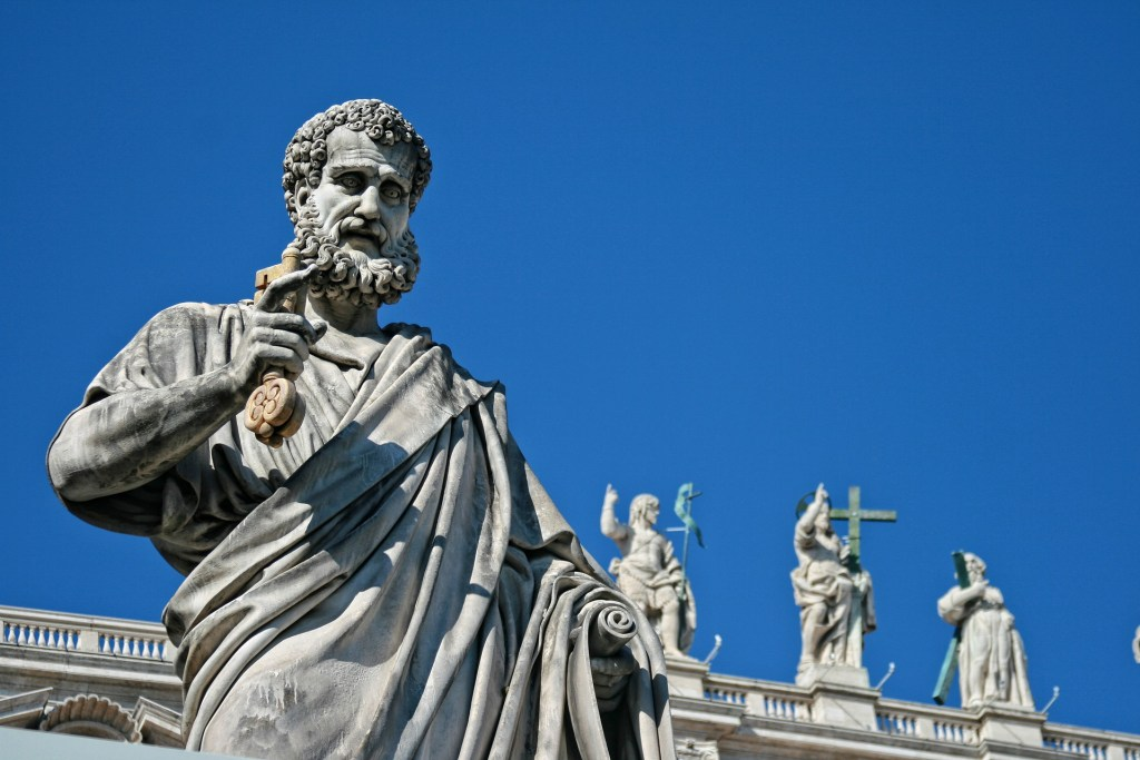 Image of statues of saints on top of a building. But Who Gets to be Saints?