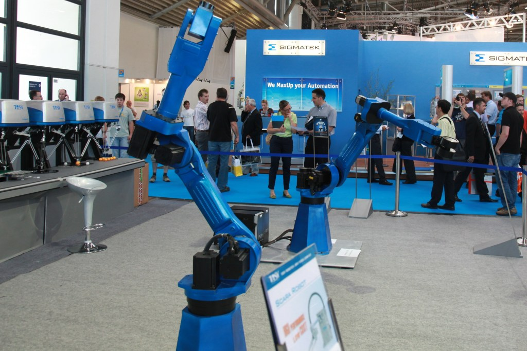 Image of an industrial robotic arm on display at a trade show.  Robots and A.I. will challenge our humanity.