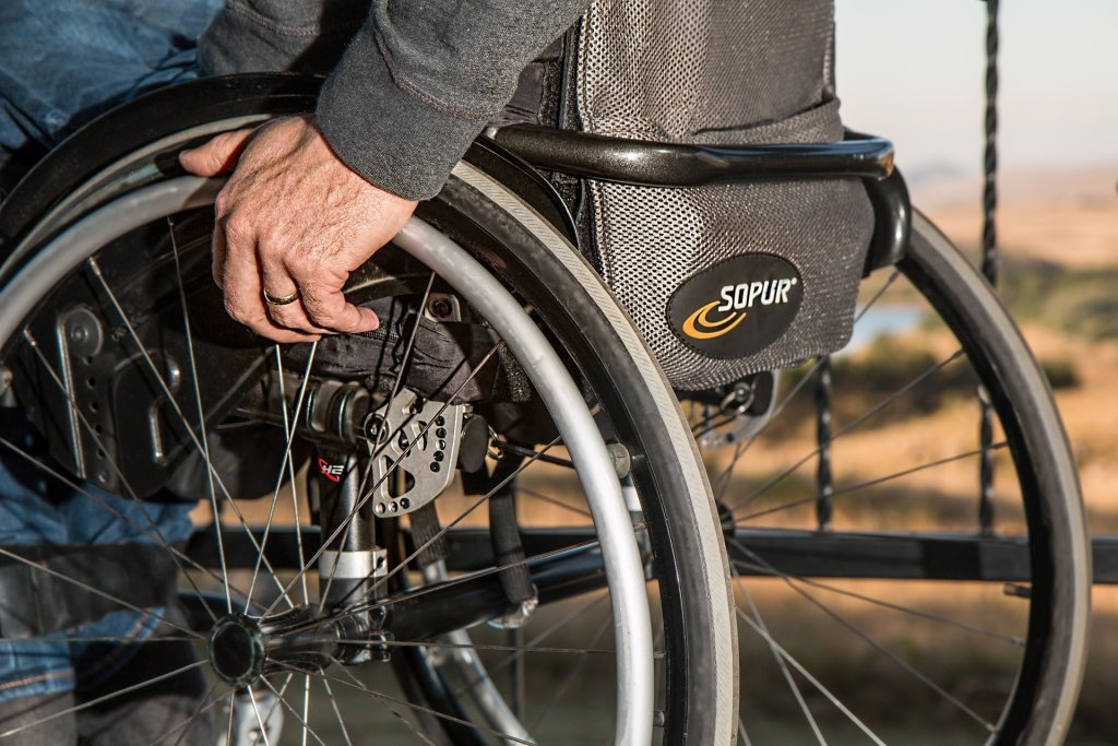 Image of a man's hand on the wheel of a wheelchair--if you had a disabling disease would you choose a head transplant?