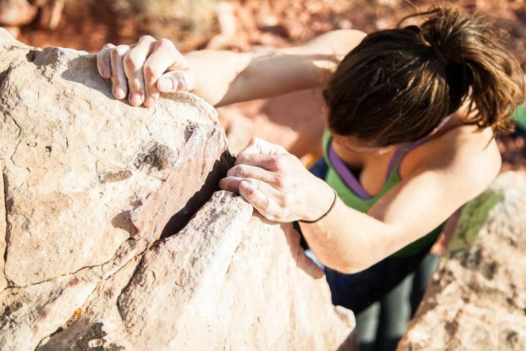 Image from the head down of a female rock climber clinging to the rocks--how it feels when I feel defeated