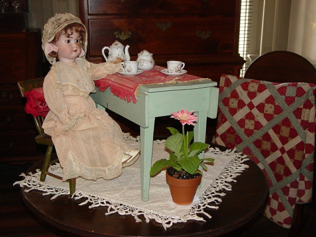 Image of old fashioned doll at tea table--a favorite game Irene played as related in her character reveal