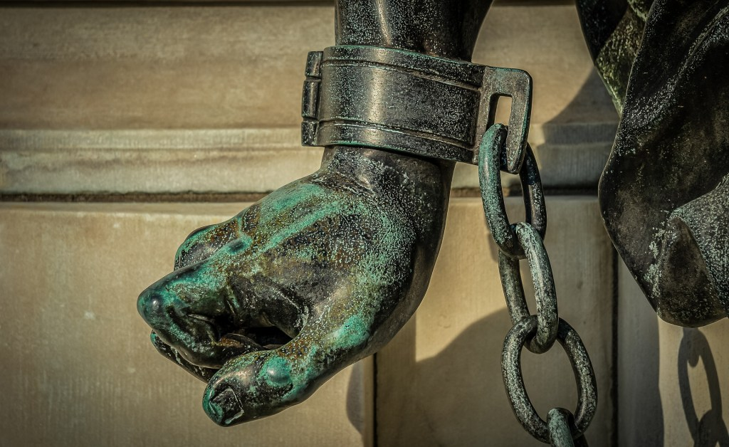 image of statue's chained hand--the reality of freedom for some is that freedom isn't real