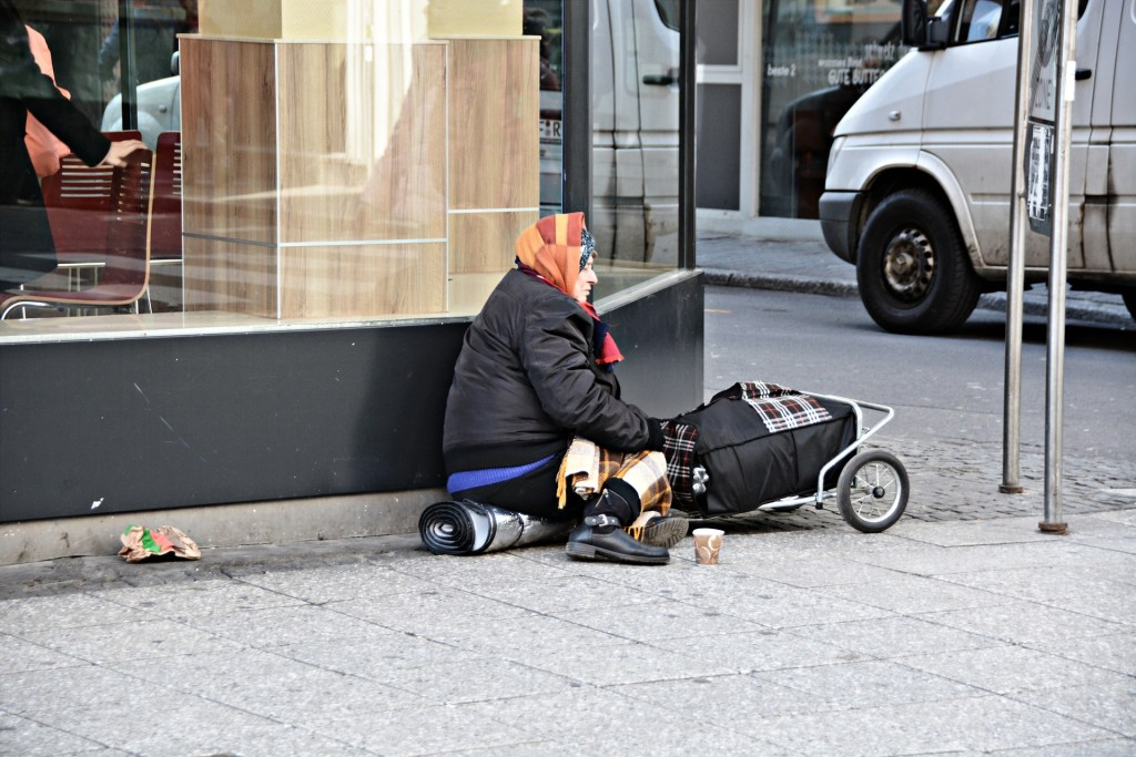Image of a homeless woman sitting with her cart of stuff--she needs a random act of love