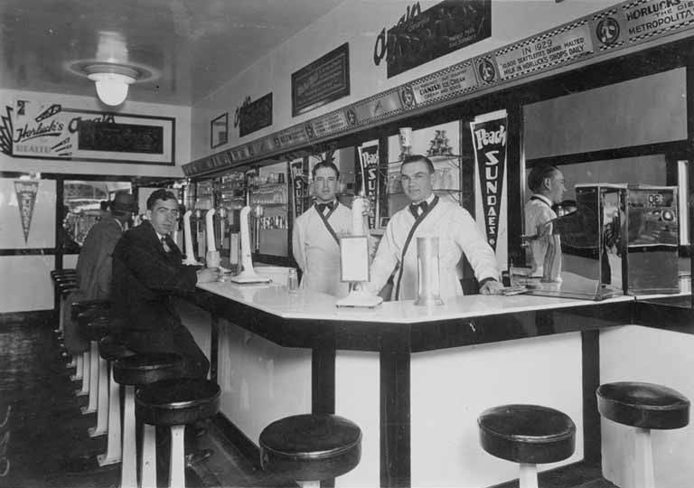 If I Should Die Chapter 5 takes place in an ice cream store like the 1950s image here of two Soda jerks behind the counter and customers waiting for their treats.