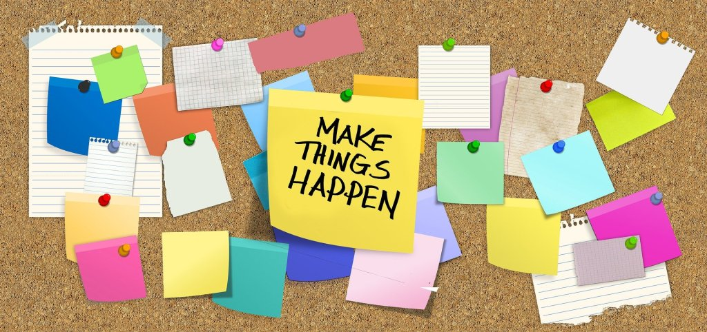 "Image of a bulletin board with a yellow post it that reads ""make things happen"""