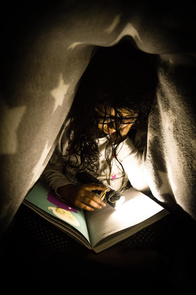 girl reading by flashlight under a blanket--you need to do a reading study and have fun doing it