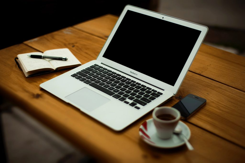image of a desktop with an open book, an open laptop  and a cup of coffee