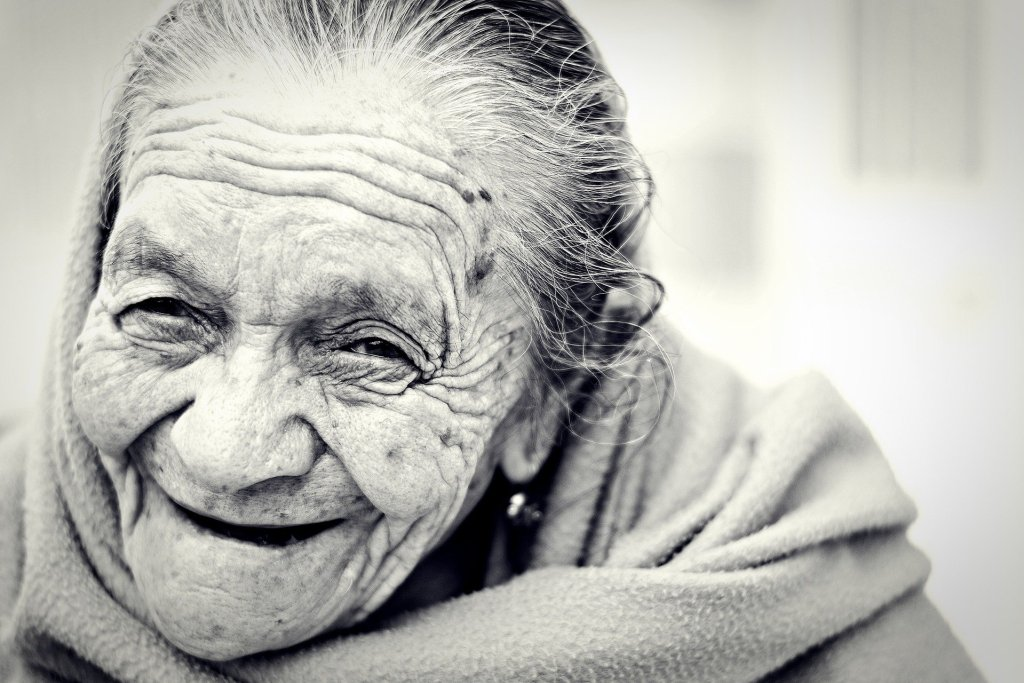 Photo of a wrinkled old woman smiling at the question how long would you want to live.