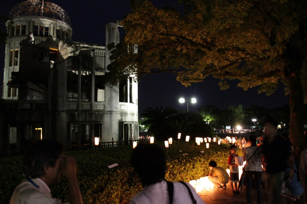 Image of the A-bomb Dome at night with paper lanterns glowing before it.