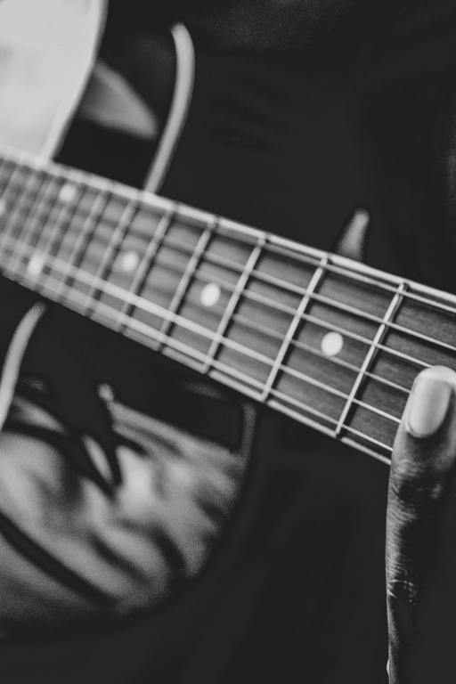 black and white image of fingers of a black person on the frets of a guitar