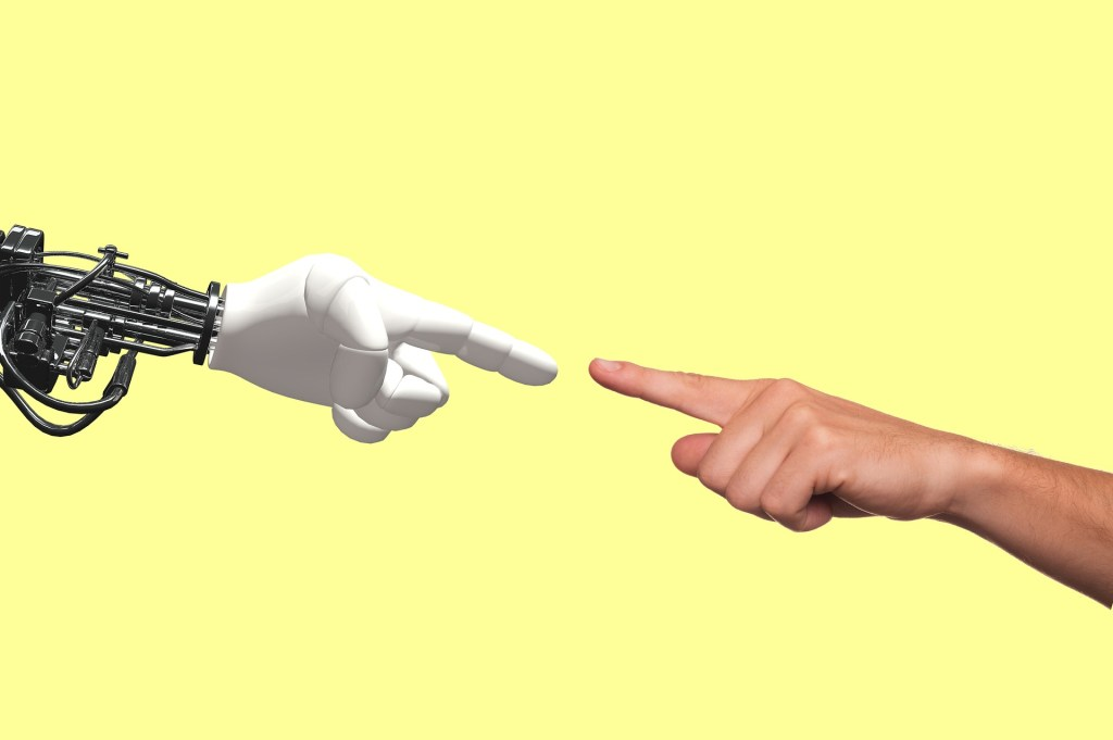 A cyborg's robotic hand points its index finger toward a human hand  pointing its index finger at the cyborg's hand
