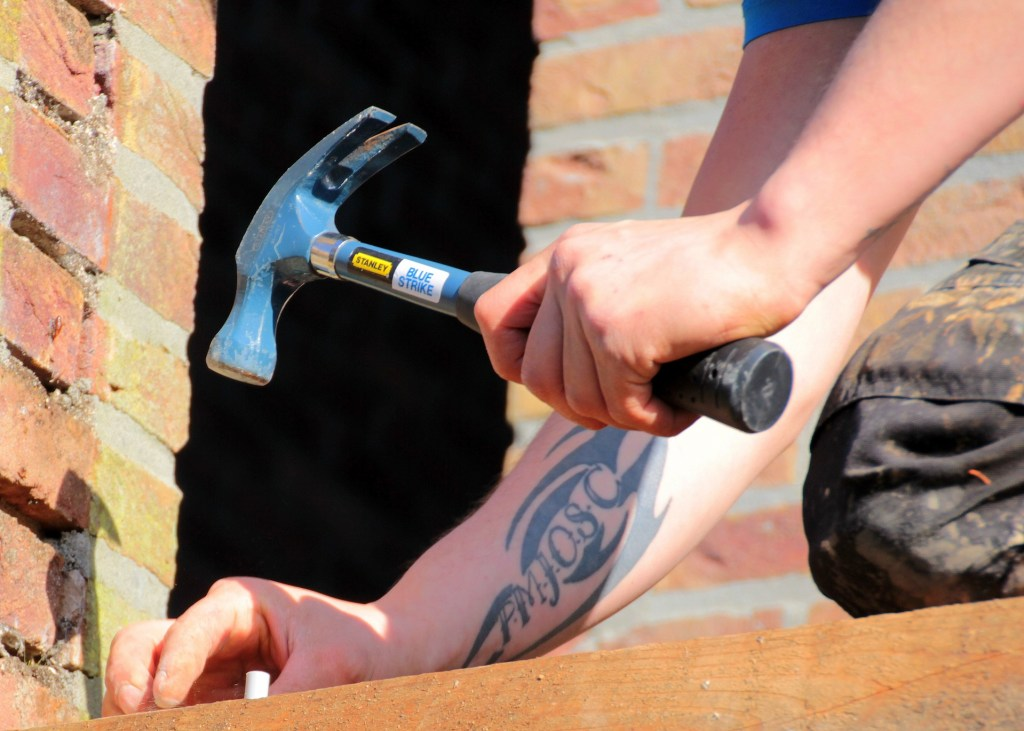 Image of the hands of a man holding a hammer about to drive a nail into a board.