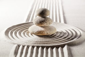 image of zen stack of flat rocks in the middle of a sand raked in a circle, a spiritual  refill is just one of the 5 ways to support your creativity