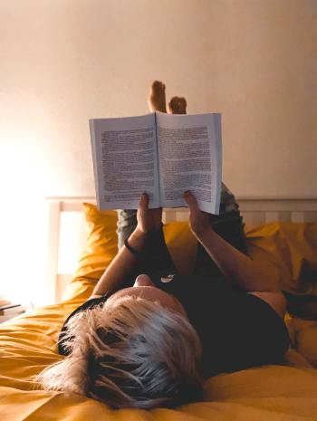 a woman  reading while laying down with her head at the foot of the bed and her feet up on her pillows and headboard