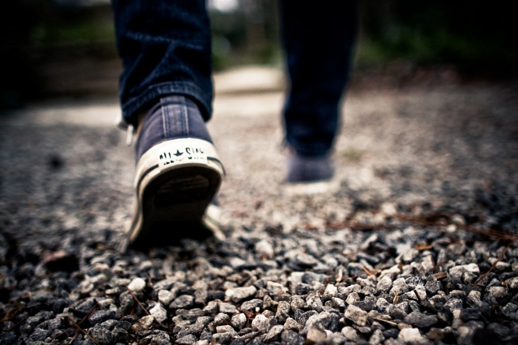 Photo focused on someone in sneakers walking away from  us across gravel--life is a journey--put one foot in front of the other