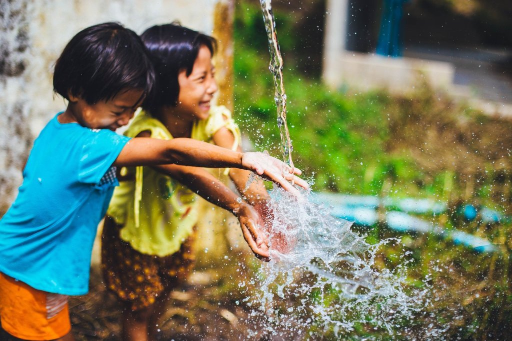 two kids playing joyfully in water--do you find your joy in water play?