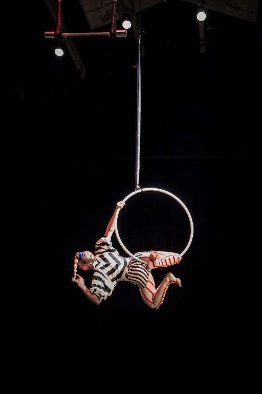 Image of a clown aerialist on a  hoop. Make your creativity fun.