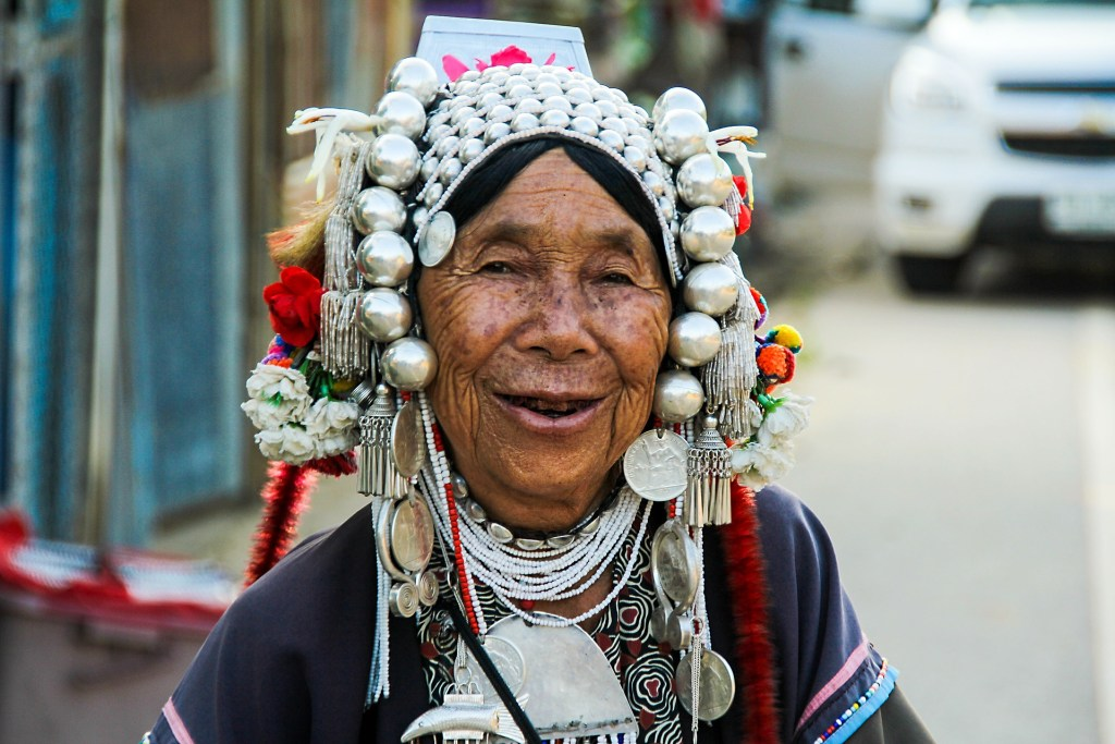 Older woman in authentic costume of her land smiling because she's allowing herself to be seen as she really is wrinkles and all