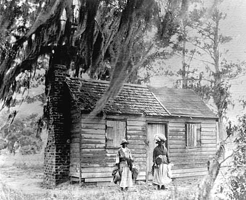 photograph of small cabin where Mary Mcleod Bethune grew up to light the way. Two young women wearing long skirts and hats stand outside the cabin
