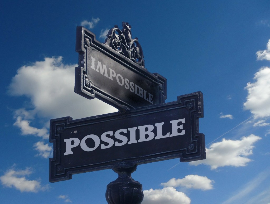 Image of street signs at the crossroads of impossible and possible--you have the strength you need--choose possible