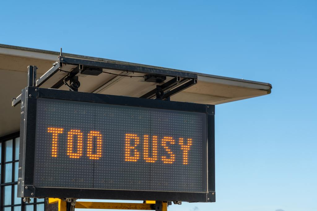 "Electronic Sign hanging from a room says ""Too Busy"""