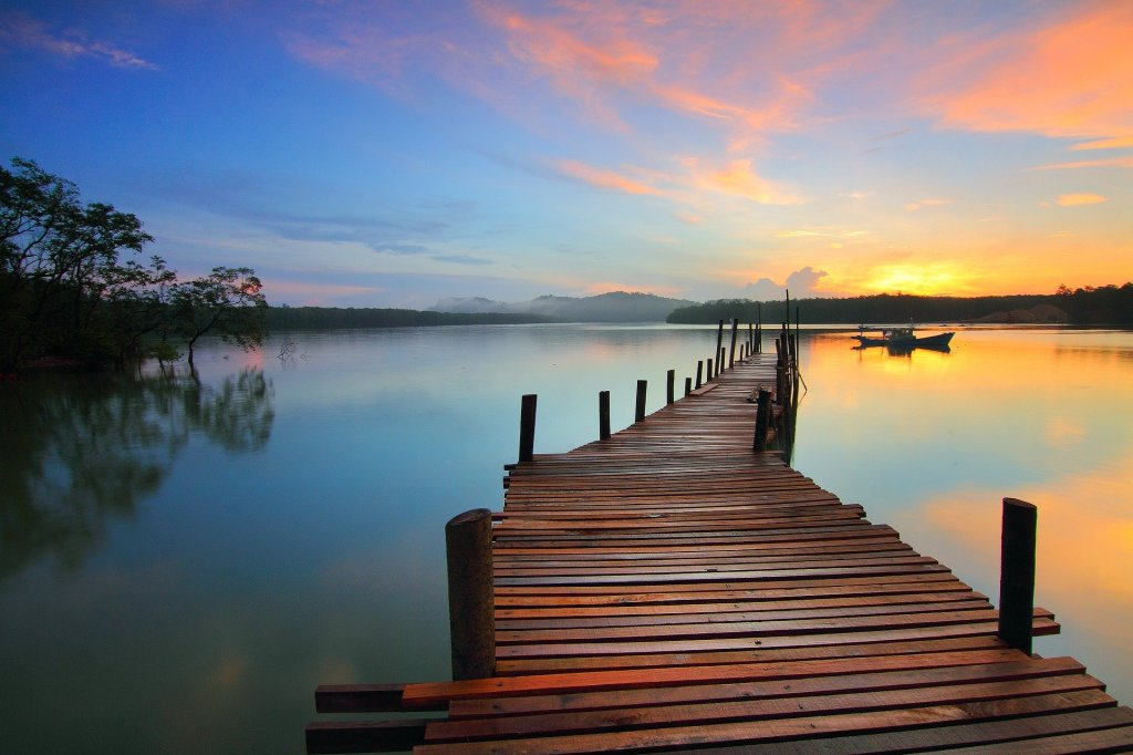 Image of a dock reaching out into a lake reflecting the morning sunrise