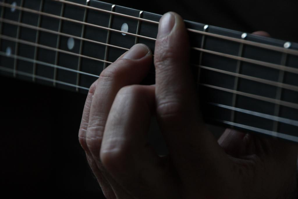 Image of a hand with fingers pressing the strings of on the neck of a guitar