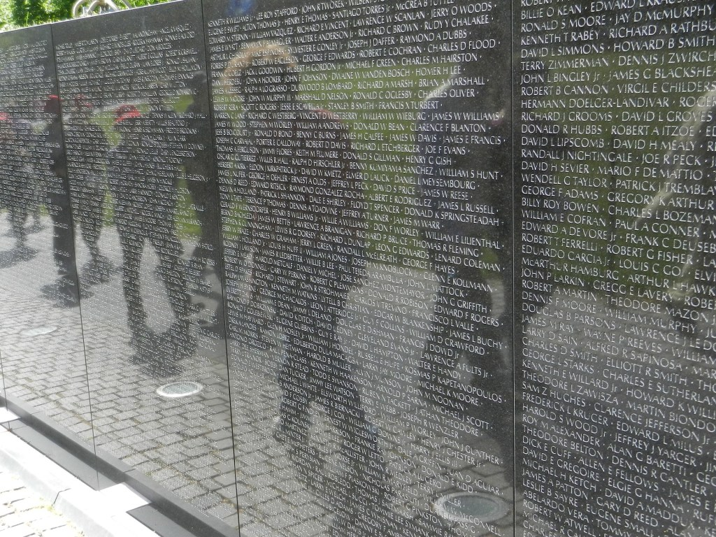 Image of the Viet Nam Memorial Wall showing reflections in the wall of people viewing it.