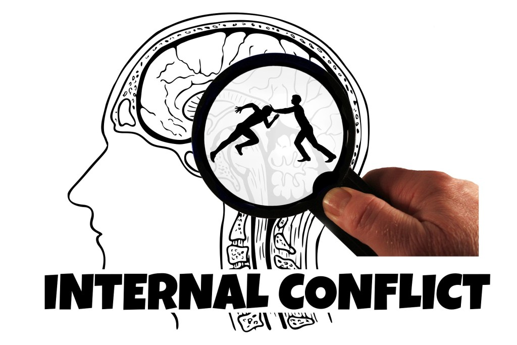 Image shows a profile of a head with the brain visible. A magnifying glass shows the silhouettes of two people one trying to run against the other whose hands are against the runners head--symbolic of self-sabotage