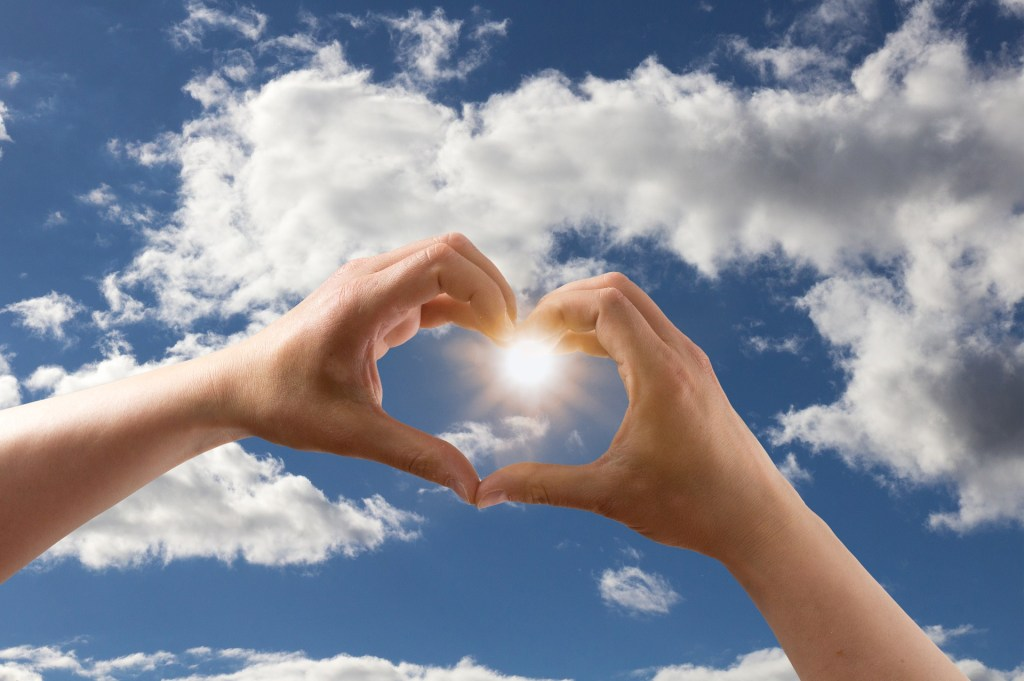 Image of  the blue sky and sun with two hands forming a heart with the sun in the center of the hands. Thank you for giving me hope