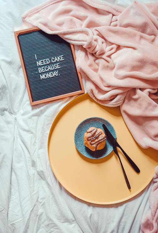 """Image background is a rumpled sheet and a rumpled pink blanket. Foreground has a sign that reads """"I need cake because Monday."""" and a yellow tray holding a blue plate of cake. Read this post Comfort for you Monday Moaning Blues"""