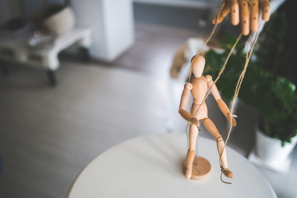 Photograph of of a wooden, blank-faced figurine controlled by strings. Breathe life into your characters by making them more than a wooden marionette.