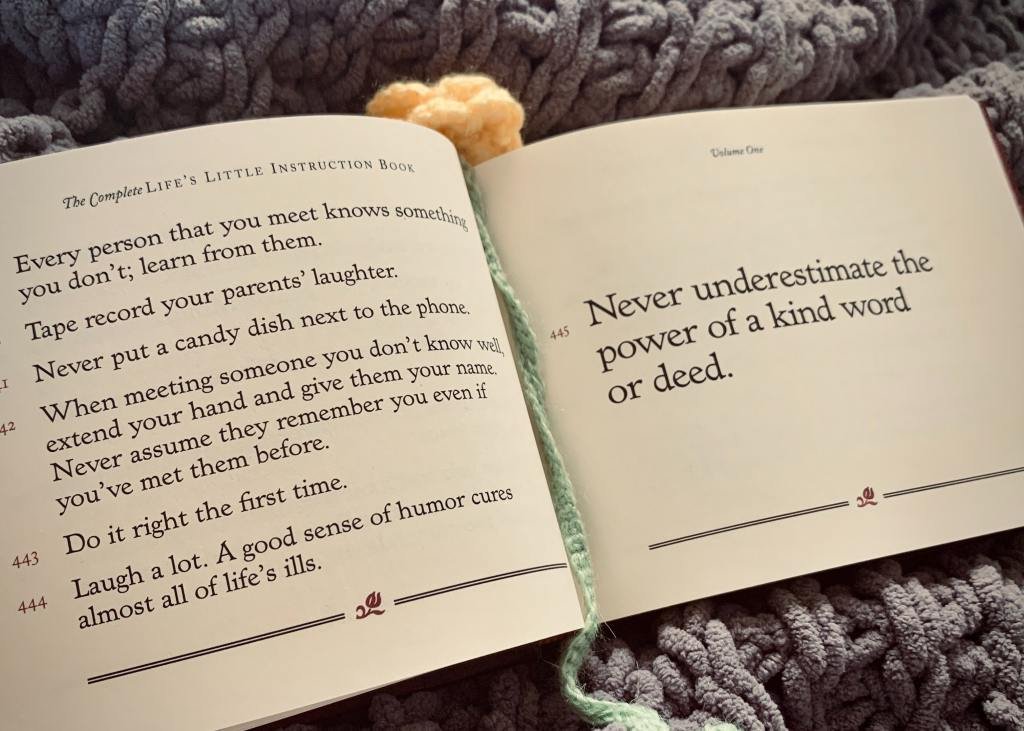"""Image of a book opened to the quote """"Never underestimate the power of a kind word or deed."""""""