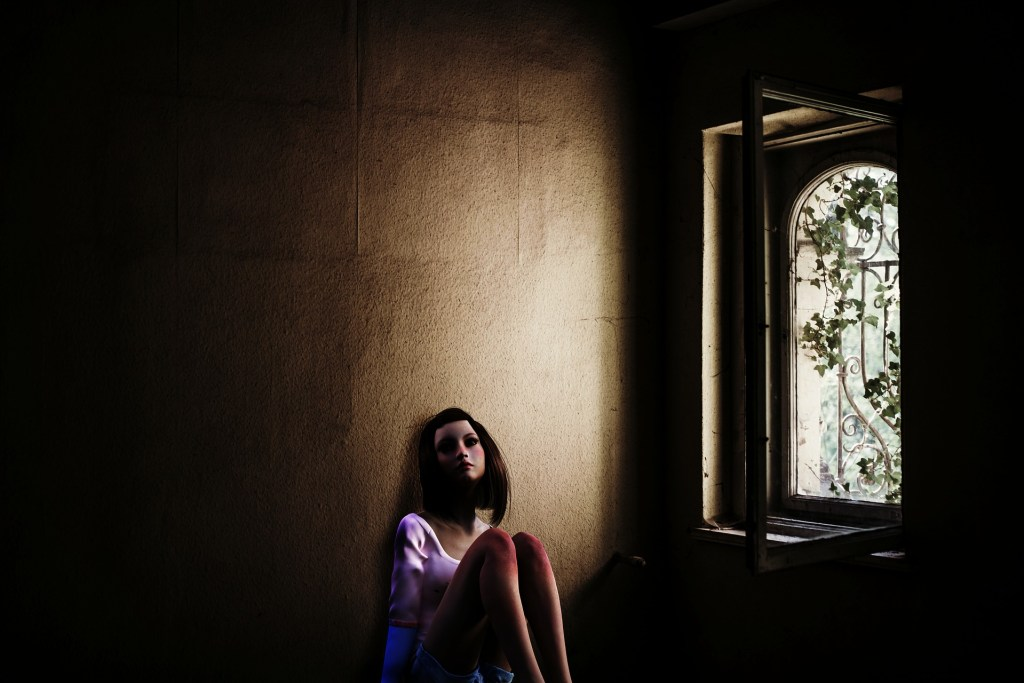 Photograph of a sad young woman sitting on the floor, against the wall. The only light from an arched stained glass window. A perfect illustration for this flash fiction friday story: Gift of a Lifetime.