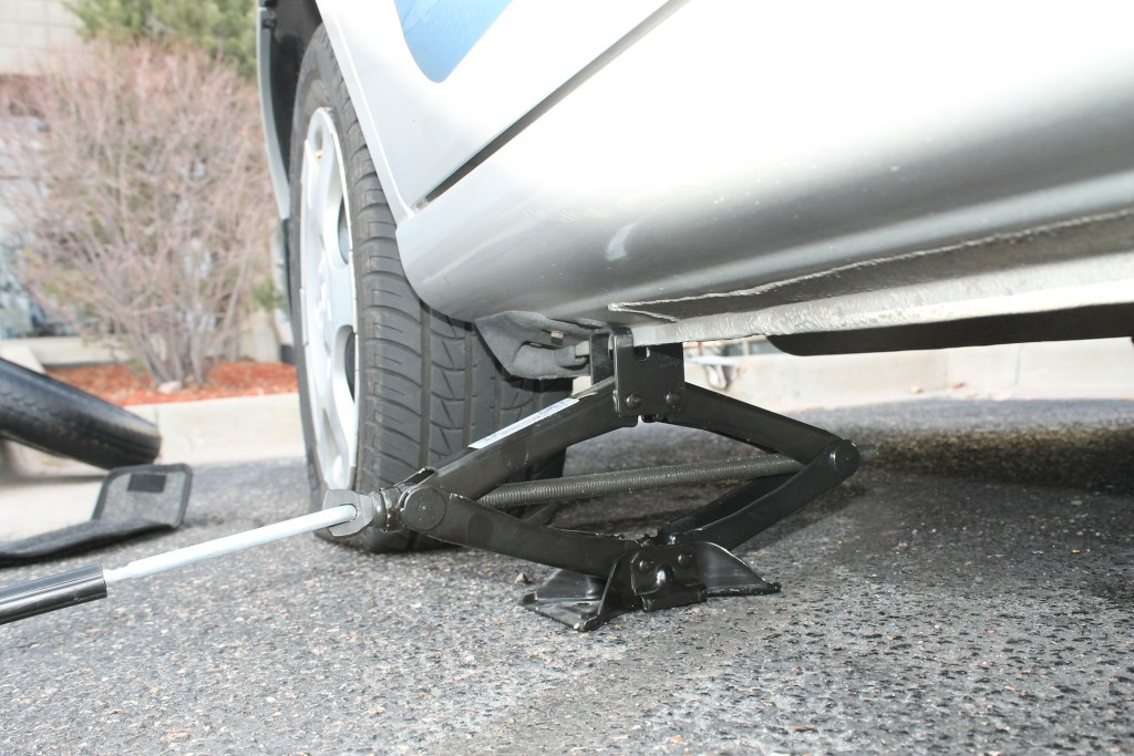 image of a silver car with a flat tire and a jack ready to be pumped in order to change the tire