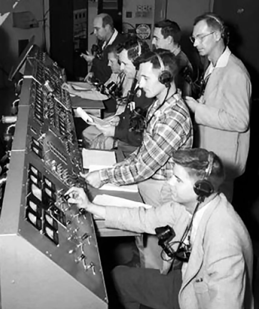 Photograph of NASA's control room in 19 with eight men crowded around control panels with dials and on off switches. Definitely not close to Star Trek Life.