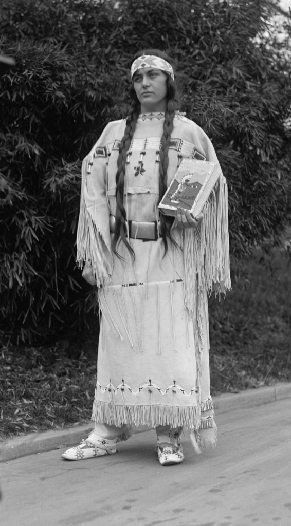 Image of Ruth Muskrat in her Plains Indian buckskin dress holding the report she presented to the President. Her history is missing from your history