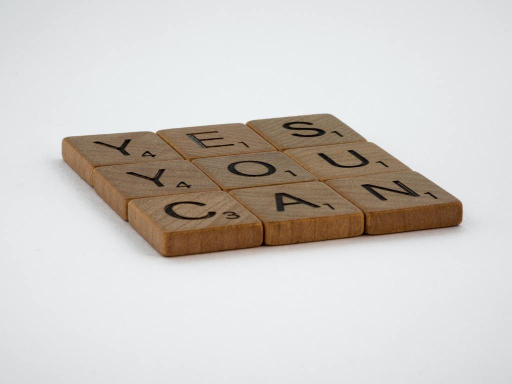 image of scrabble tiles placed in a square spelling out yes you can.