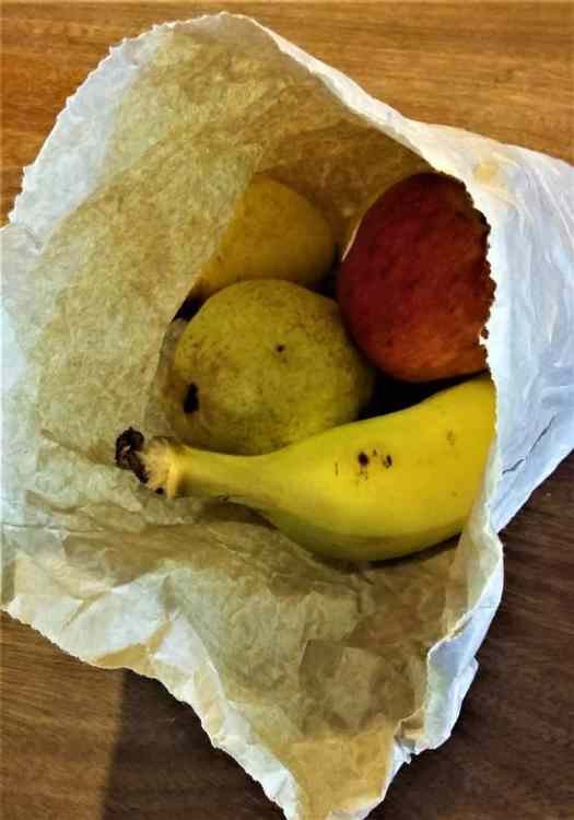 Pears and bananas in a paper bag to ripen