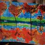 Child's painting of autumn trees reflected in water.