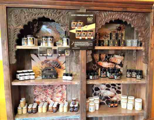 Decorative wooden cabinet displaying honey products.