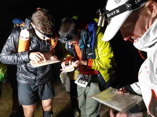 Three competitors study their maps in the dark, moments before the race begins.
