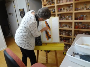Lynn Bridge checking a mosaic project in her art studio