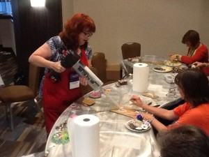 Woman using an epoxy gun at the SAMA 2014 conference in Houston, Texas.