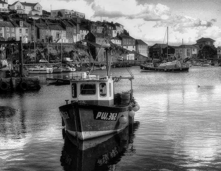 black and white boat in Mevagissey harbour Cornwall