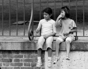 A boy and a girl, about 10 years old, dangle their feet over a ledge at the edge of an elevated walkway through a city park.