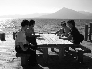 Four teenage boys sit around a picnic table on a beach talking, with ocean and mountains and a clear sky in the background.