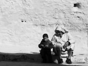 An older man and a little boy sit on the ground in front of a large white stucco wall.
