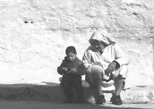 An older man and a little boy sit on the ground talking in front of a gray stucco wall.