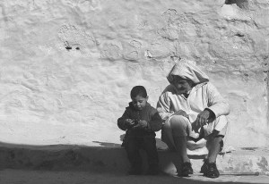And older man and a little boy sit on the ground in front of a large gray stucco wall.